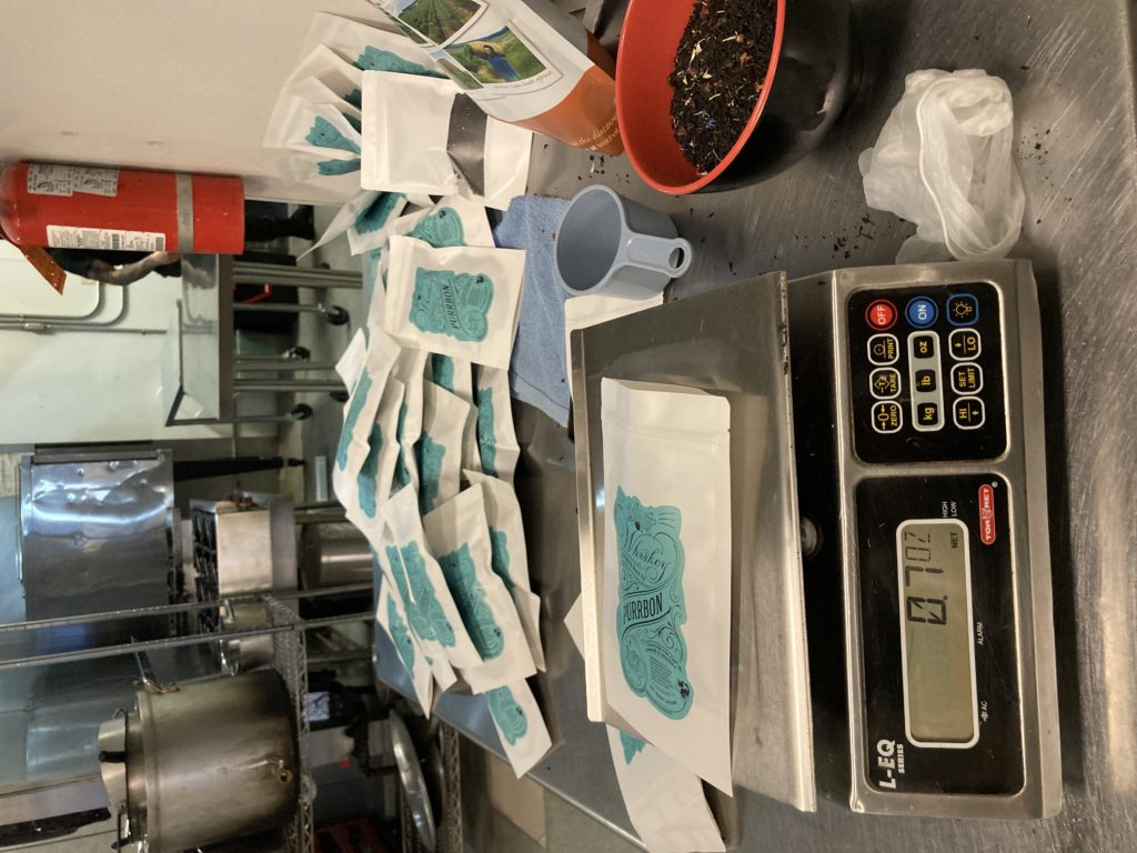 A commercial kitchen counter showing a bowl of tea, a commerical food scale and dozens of bags of tea being packed.