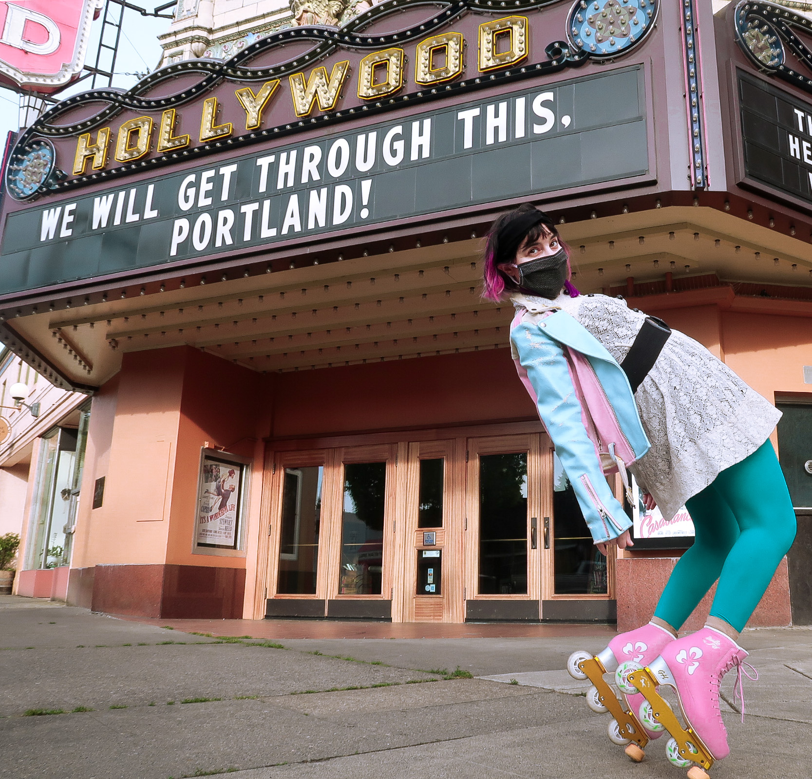 """Me in a white dress and pink and blue motorcycle jacket balancing on pink roller skates, with a marquee behind me that says """"we will get through this, portland"""""""